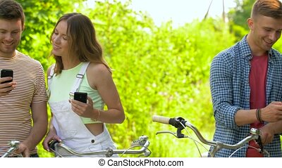 friends with bicycles and smartphones at park - people,...