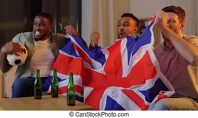 friends with british flag watching soccer at home - ...
