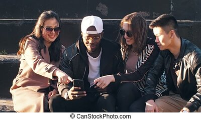 Friends with cellphone sitting on the street - Group of...