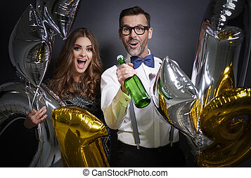 Friends with champagne bottle and balloons
