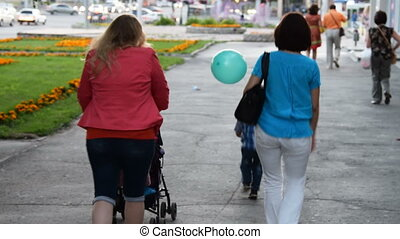 Friends with children walking in the city