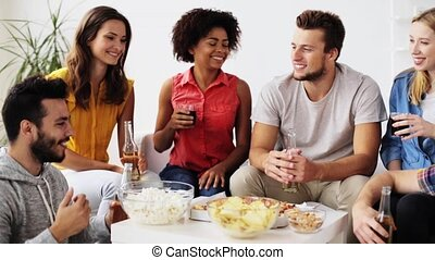 friends with drinks and snacks talking at home