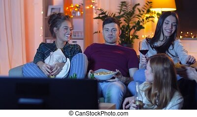 friends with drinks and snacks watching tv at home -...