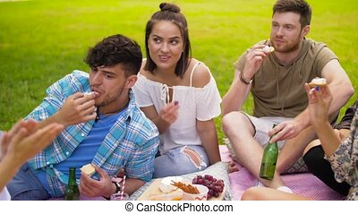 friends with drinks eating food at summer picnic -...