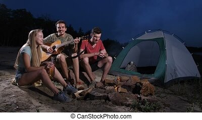 Friends with drinks playing guitar at camping
