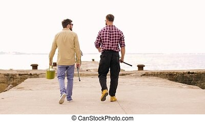 friends with fishing rods walking along pier - leisure and...