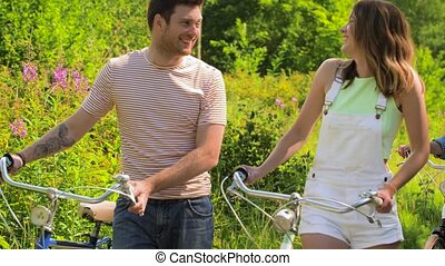 friends with fixed gear bicycles walking in park