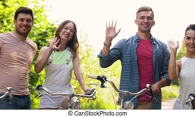 friends with fixed gear bicycles waving hands