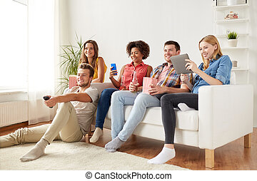 friends with gadgets and beer watching tv at home - ...