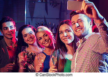 friends with glasses and smartphone in club - party, ...