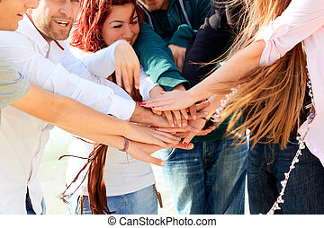 friends with hands together - young casual friends putting...