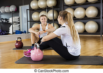Friends With Kettlebells On Exercise Mat In Gym