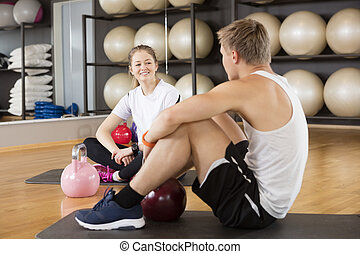 Friends With Kettlebells On Exercise Mat In Gymnasium