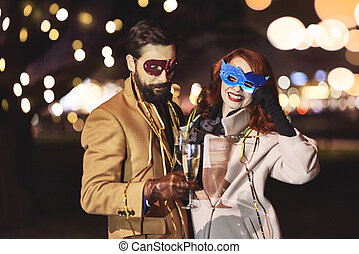 Friends with mask and champagne flute toasting