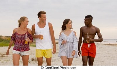 friends with non alcoholic drinks walking on beach - party,...