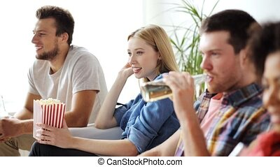 friends with popcorn and beer watching tv at home