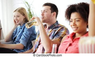 friends with popcorn and beer watching tv at home -...