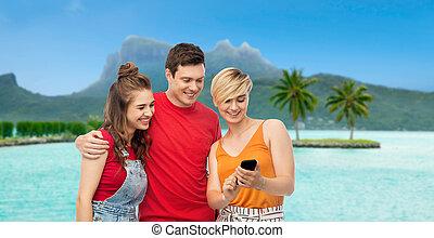 friends with smartphone over bora bora beach