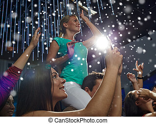 friends with smartphone taking picture at concert