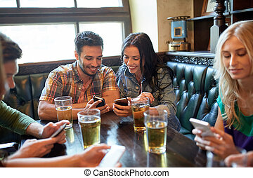 friends with smartphones and beer at bar or pub - people,...