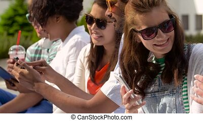 friends with smartphones and tablet pc in city - technology,...