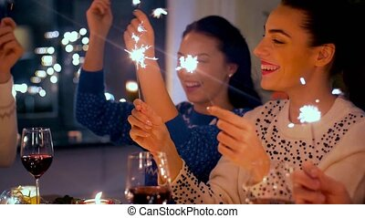 friends with sparklers at home christmas dinner - holidays...