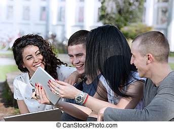 Friends with tablet on bench - Group of young students...