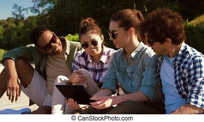 friends with tablet pc on wooden terrace in summer -...