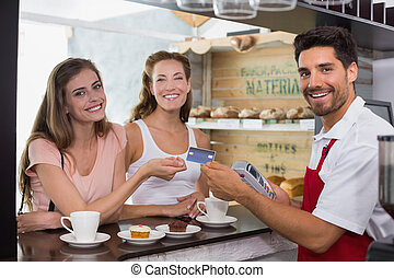 Friends with woman holding out credit card at coffee shop -...