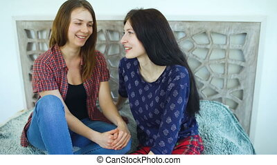 friends women blonde and brunette sitting bed whispering in...