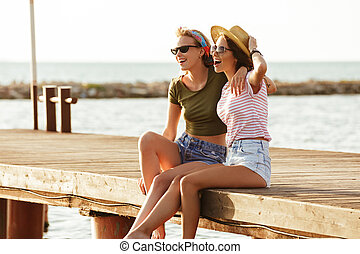 Friends women sitting outdoors on the beach looking aside.