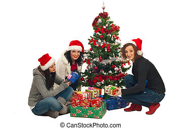 Friends women with Christmas tree and gifts