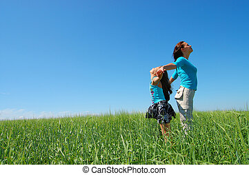Friendship and happiness of mum and daughter against the blue sky