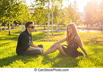 Friendship and love concept with a young couple sitting on the grass and talking.