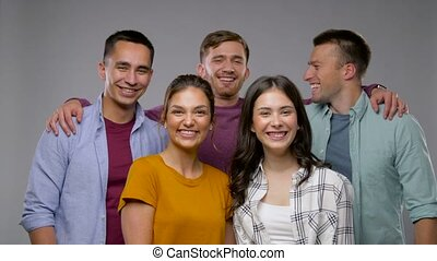 group of happy smiling friends over grey