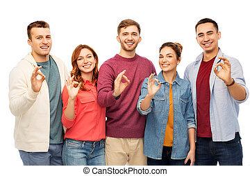 group of smiling friends showing ok hands sign