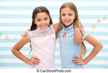 Friendship as treasure concept. Kids schoolgirls preteens happy together. Friendship from childhood. Girls smiling happy faces hug each other stand striped background. Girls children best friends hug