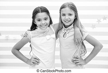 Friendship as treasure concept. Kids schoolgirls preteens happy together. Friendship from childhood. Girls smiling happy faces hug each other stand striped background. Girls children best friends hug