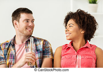 happy friends or couple with beer talking at home