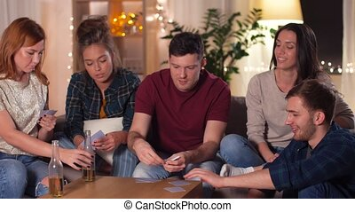 friends playing cards game at home in evening - friendship,...