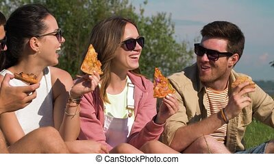 friends eating pizza at picnic in summer park - friendship,...