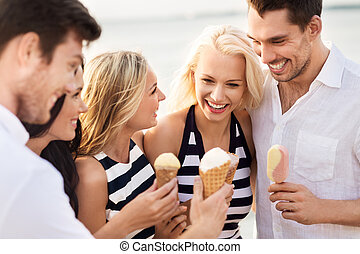 happy friends in striped clothes eating ice cream