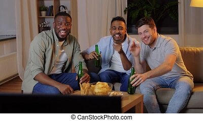 male friends drinking beer and watching tv at home - ...