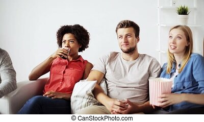 friends with popcorn and drinks talking at home