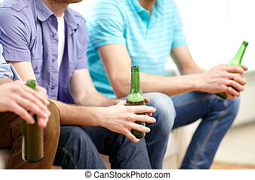 happy male friends drinking beer at home