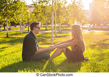 friendship, leisure, summer and people concept - young love couple sitting on grass in park