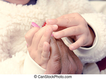 Friendship - Old woman and young girl holding hands...