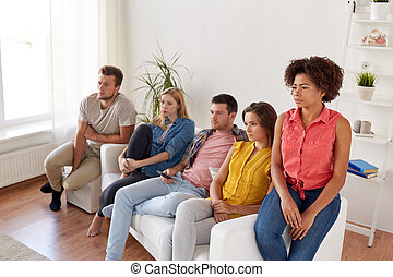 sad friends watching tv at home