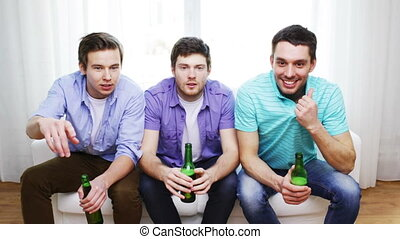 happy male friends with beer watching tv at home