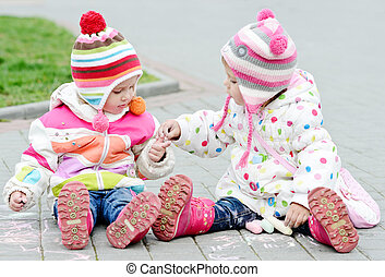 friendship - two toddler girls are playing and drawing with...